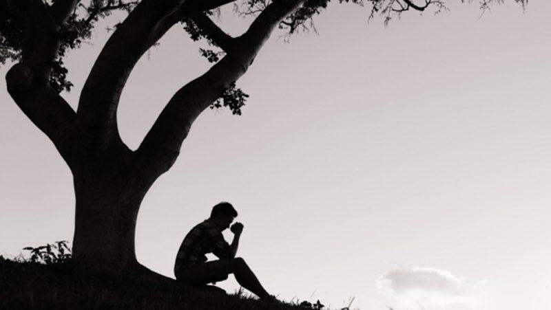 木下でうつむく男性